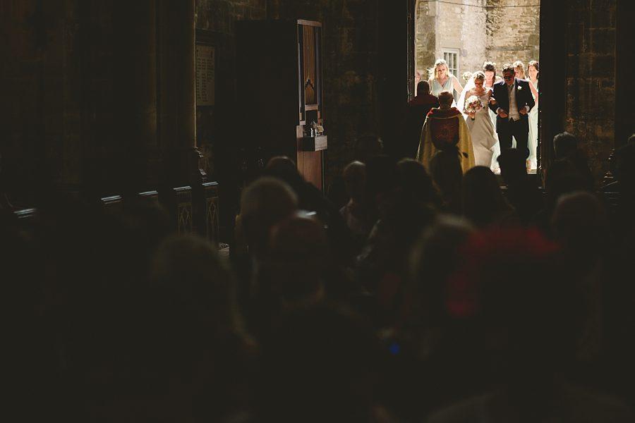 bride entering cirencester church by sam gibson