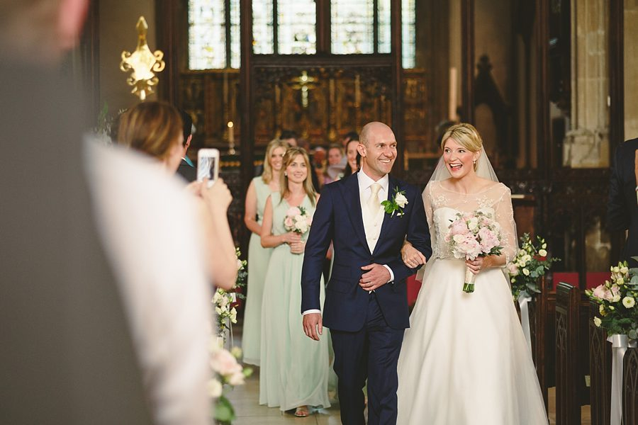 bride and groom leaving cirencester church by sam gibson