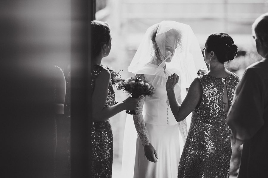 bride adjusting veil at her wedding in norwich by sam gibson