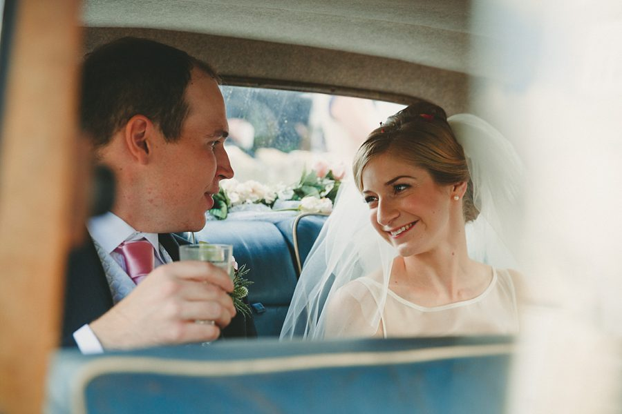 bride and groom in their morris minor wedding car
