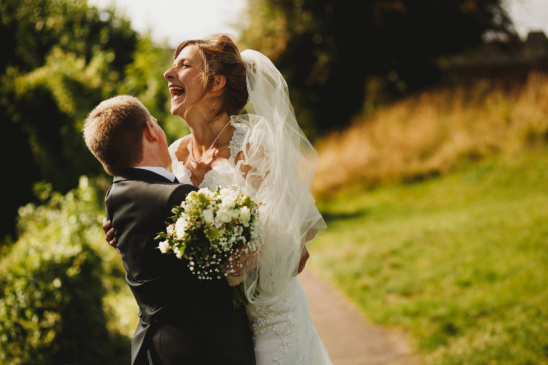 groom picking up bride and laughing