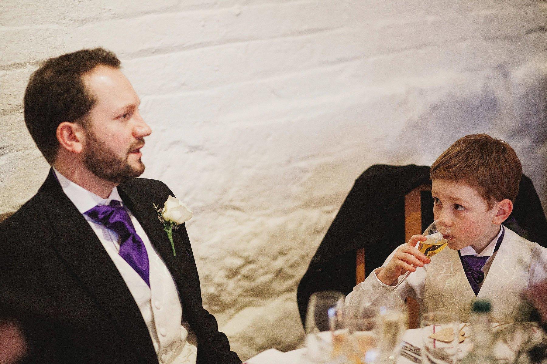 boy sips champagne at wedding