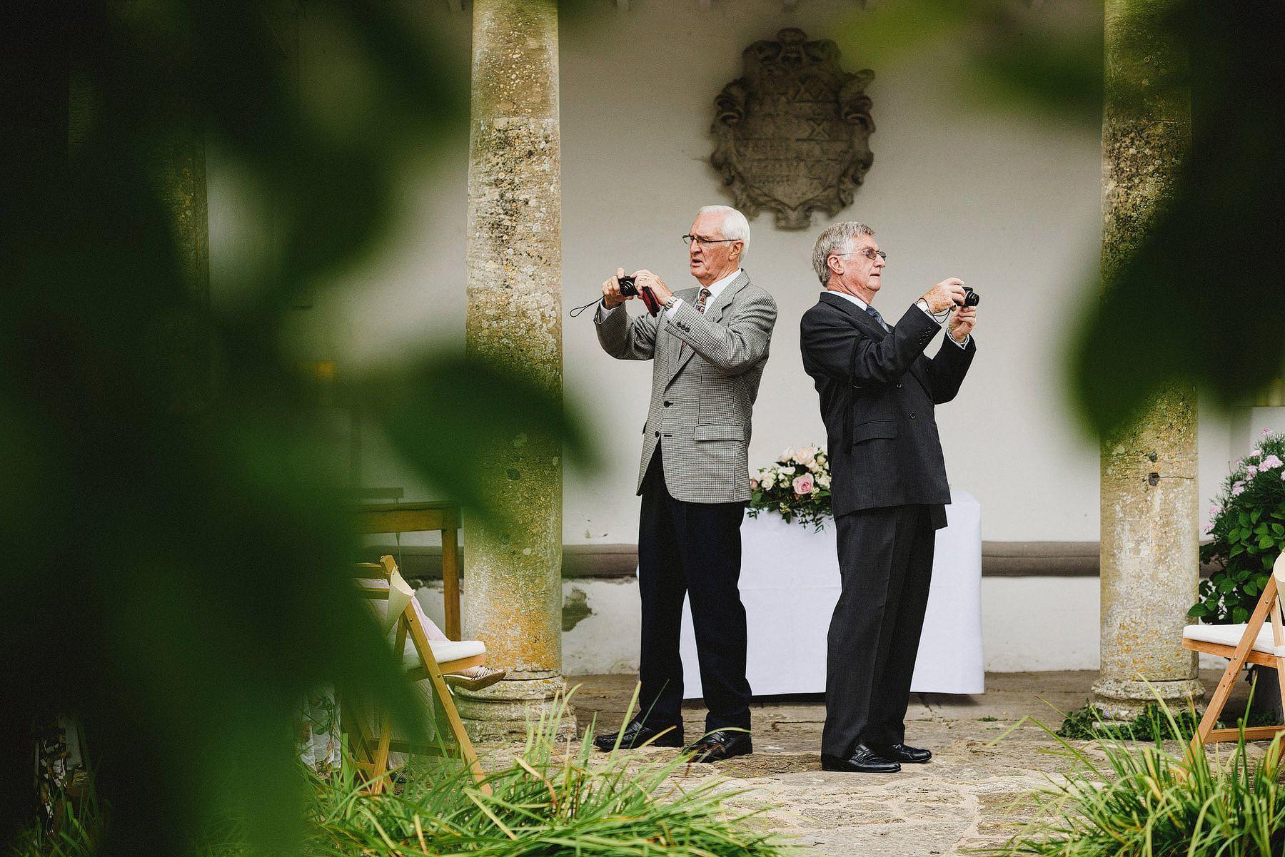 two guests taking photos at barnsley house wedding