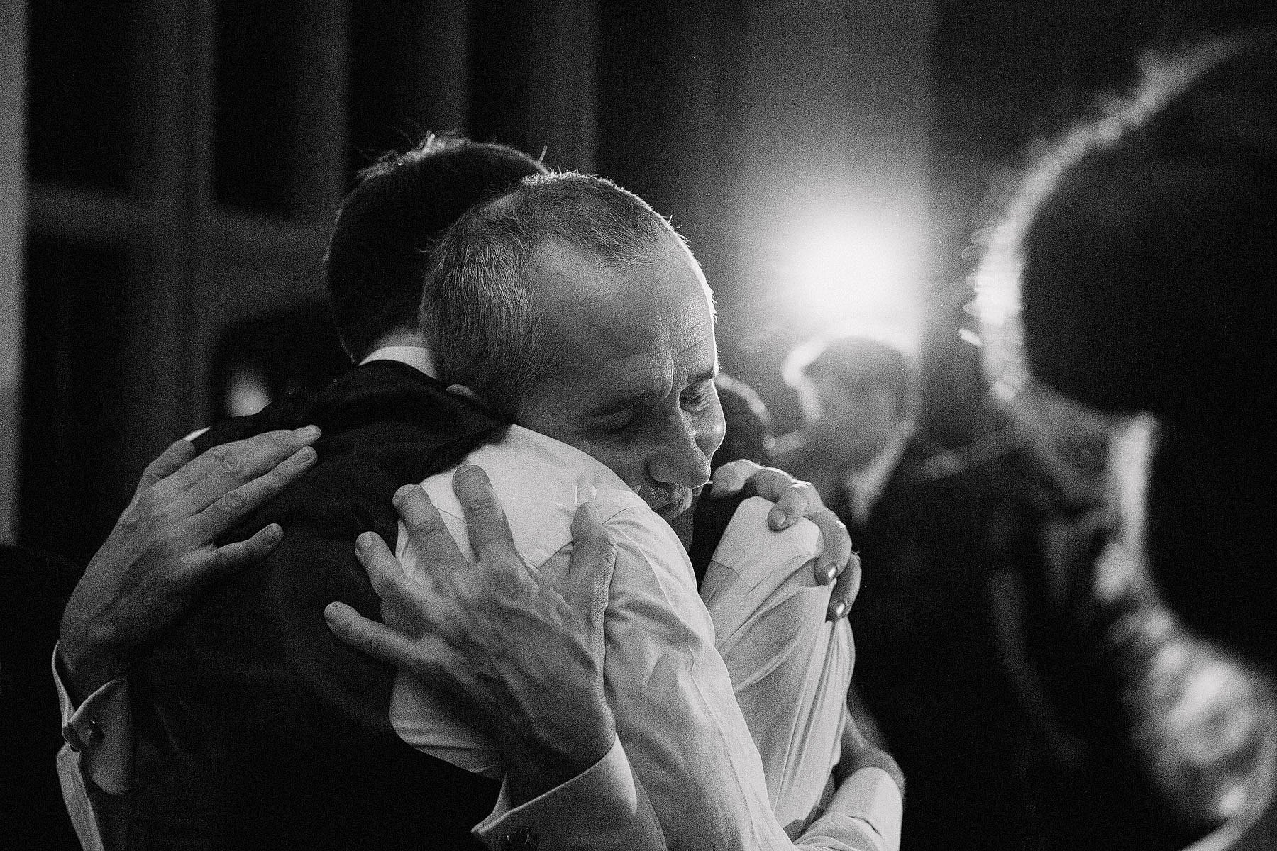 father and son hug at wedding