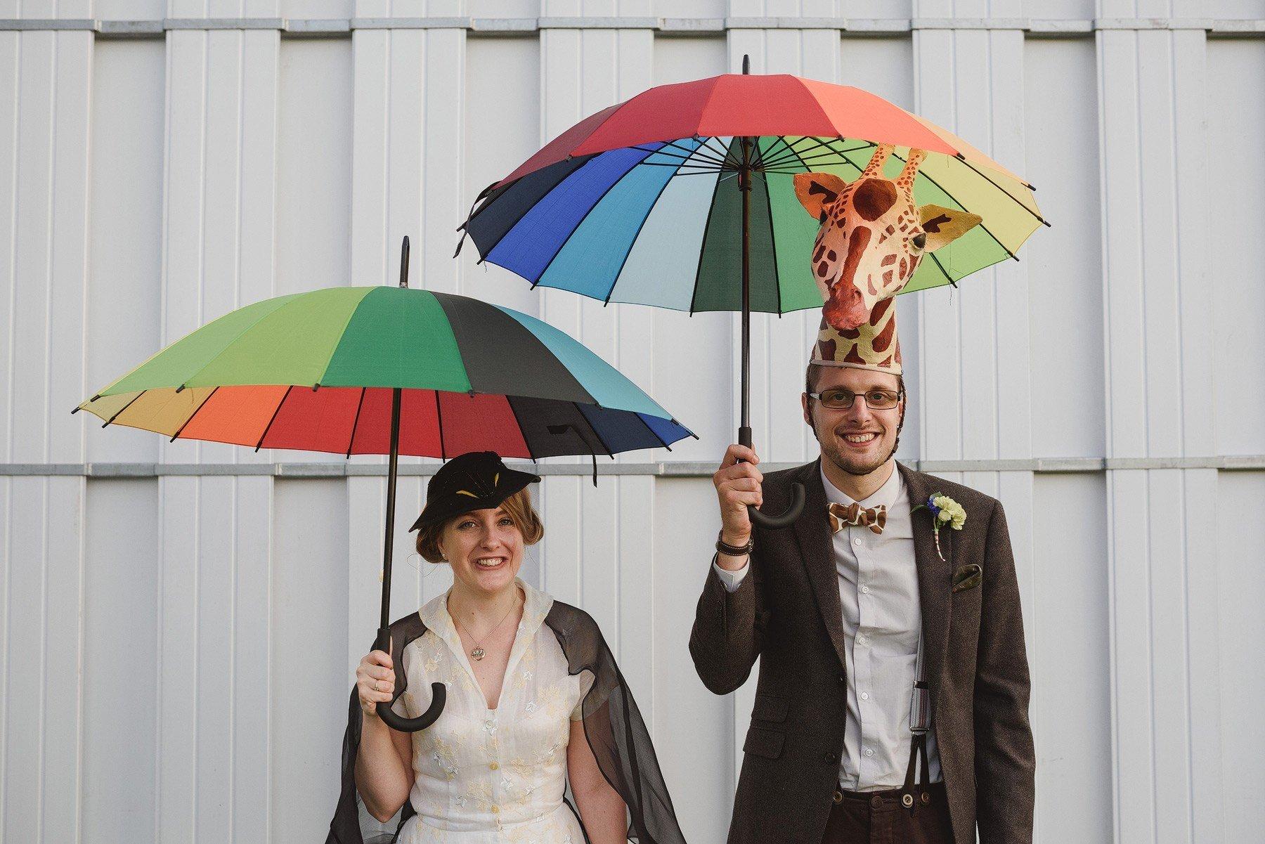 alternative portraits at a wedding using rainbow umbrellas