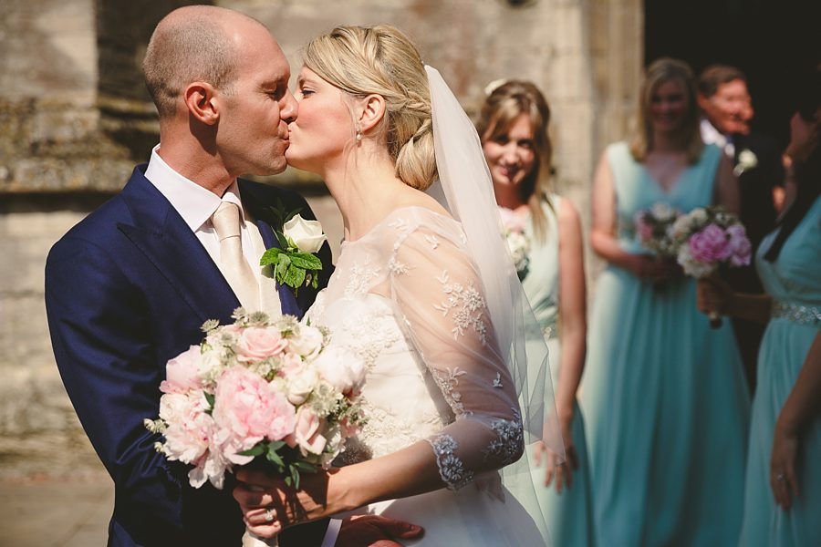 bride and groom kissing outside cirencester church by sam gibson