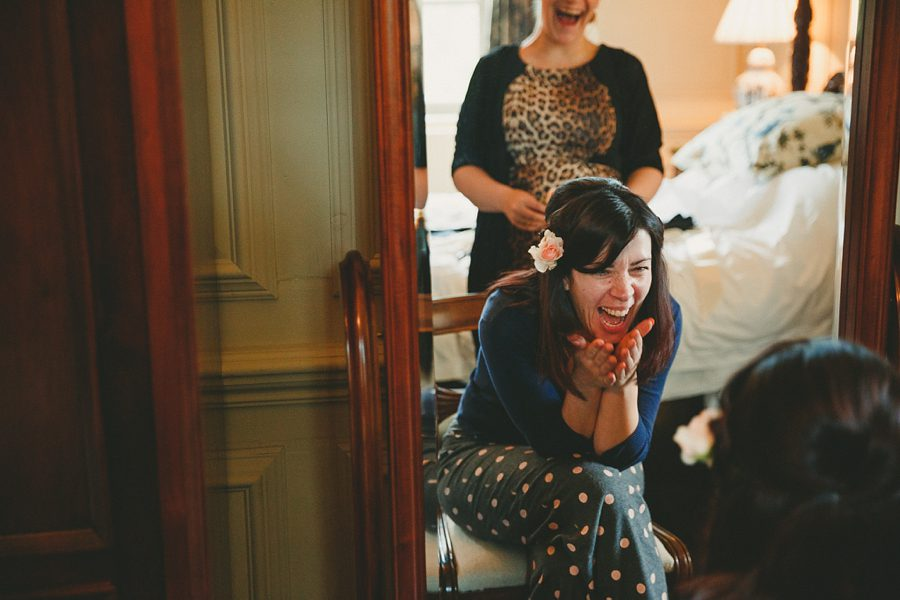 bride having make-up applied and laughing