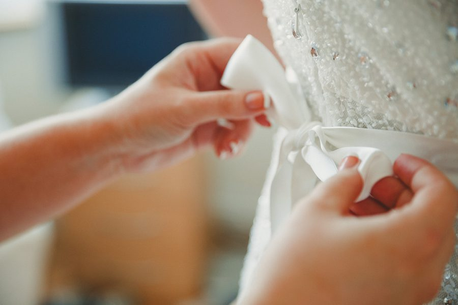 bridesmaid doing up a wedding dress