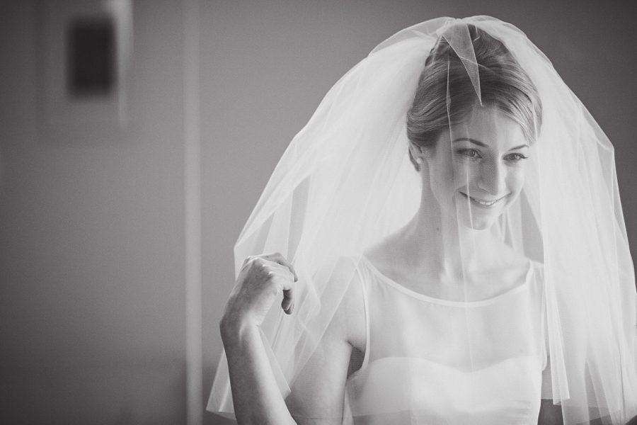 bride adjusting her veil at home