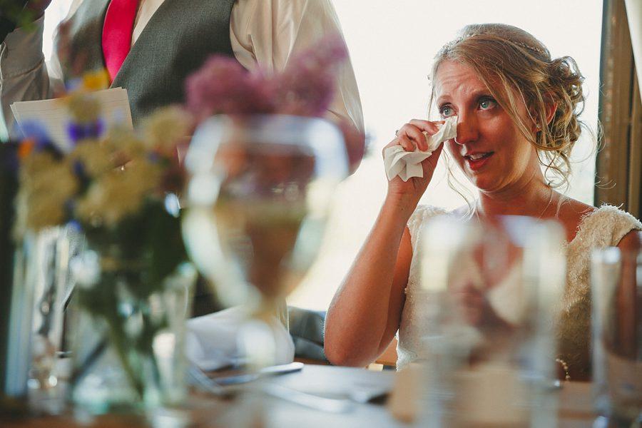 bride wipes eye during speech at a wedding in dittisham
