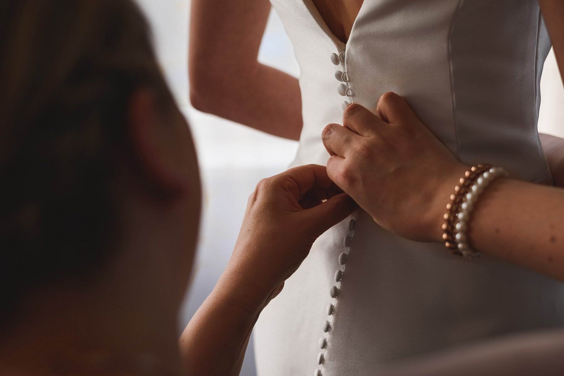 bridesmaid doing up wedding dress