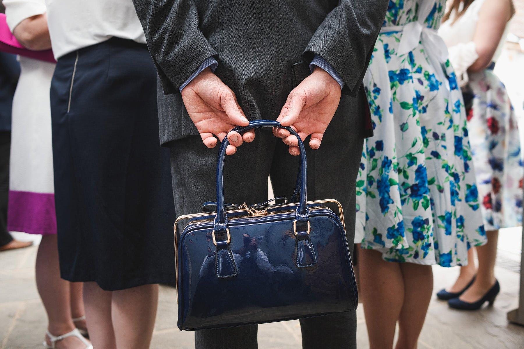 man holding handbag at a wedding
