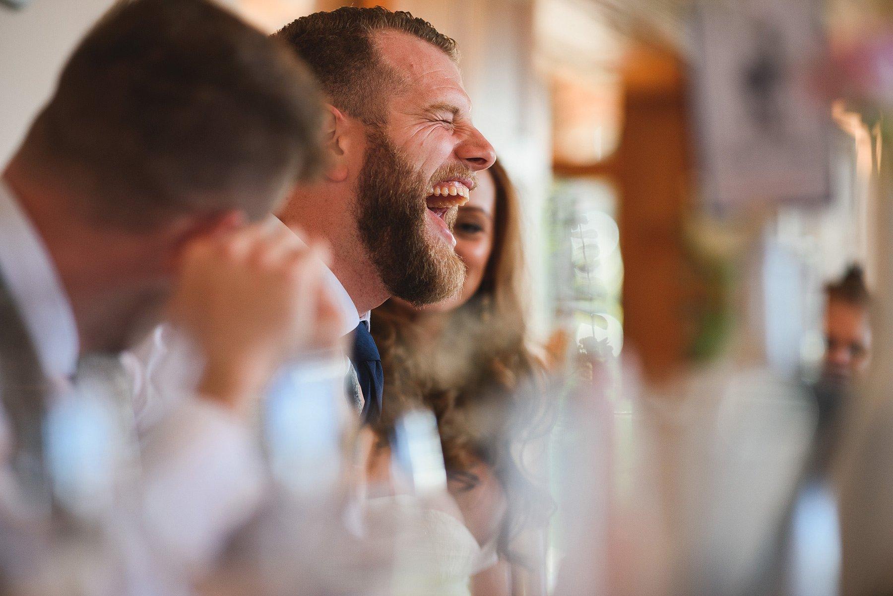 man laughing at wedding speech